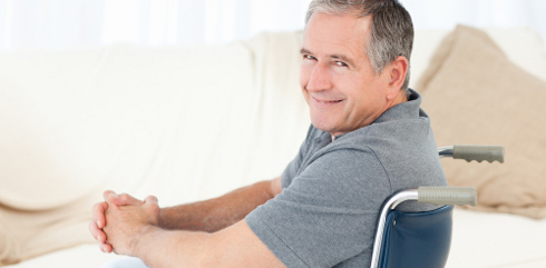 Mature man in his wheelchair looking at the camera at home